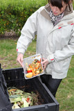Woman making compost from old vegetables