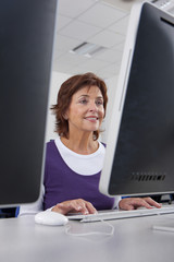Smiling adult student studying in college evening class computer lab