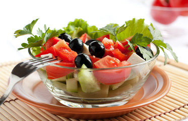 Juicy Greek salad in  glass salad bowl