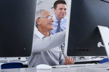 Teacher talking with adult student in college evening class computer lab