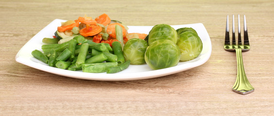 Mixed vegetables on plate on wooden table on green background