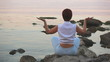 The girl sits on the seashore in a pose of meditation by a back
