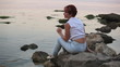 The woman sits on the seashore and turns around with a smile