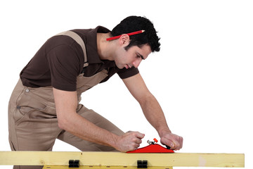 A male carpenter using a plane.
