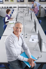 Smiling teacher teaching in college evening class computer lab