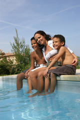 Mother and kids sitting at the poolside