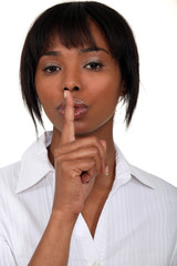 Woman holding her index finger to her lips