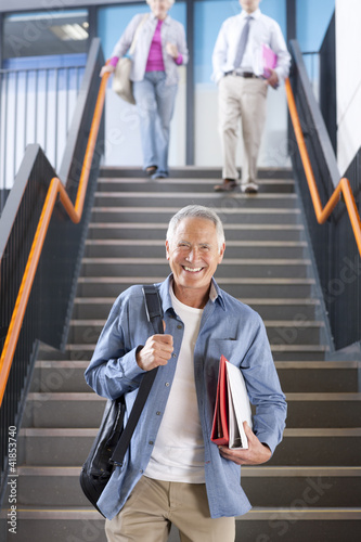 Adult students walking down stairs in college arriving for evening classes
