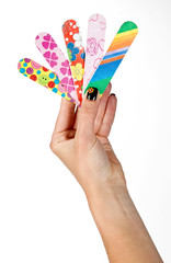 woman manicured hand holding collection of nail files