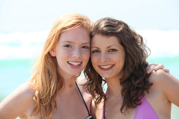 Two friends standing  on the beach