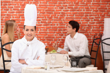 female chef posing in restaurant with couple dining