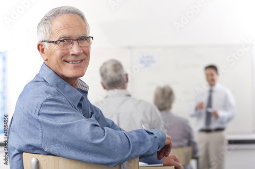 Smiling man turning in seat during college evening class