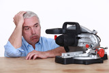Man with circular saw looking fed-up