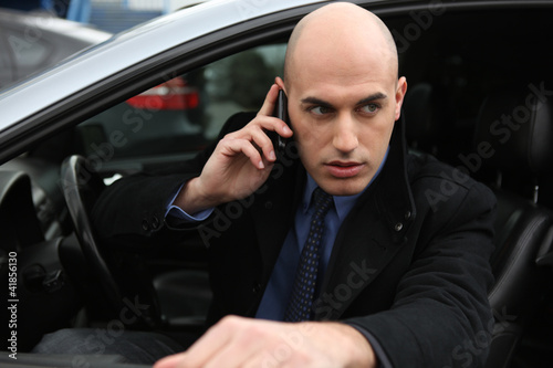 Man with mobile phone in car