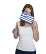 Attractive woman hides her face behind Greece flag