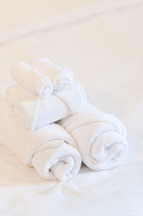 bath towels rolled on white bed