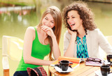 Fototapety Two beautiful women laughing over a cofee