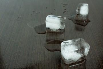 ice cubes on wet wenge wood table background