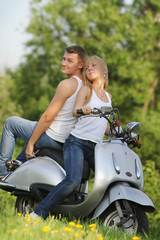 young loving couple on motorbike / scooter on natural background