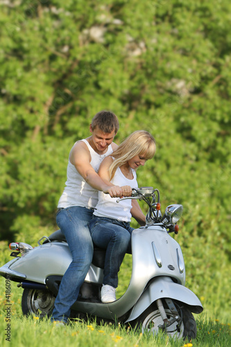 young happy couple on motorbike / scooter on natural background