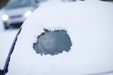 Woman peering from hole in snow on car windshield