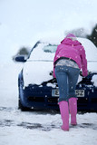 Woman pushing snow covered car in snowfall