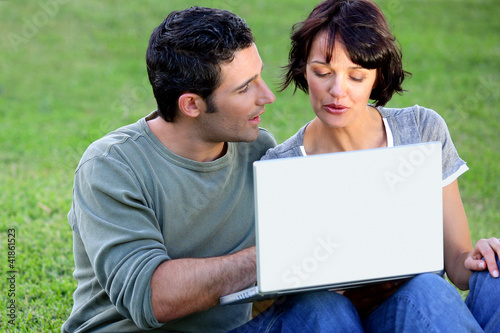 Couple making use of free wifi in the park