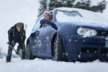 Woman in car watching man shoveling snow from around car