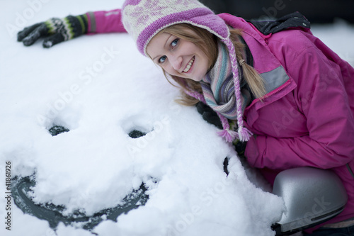 Woman making a face in snow on car windshield