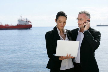 Two businesspeople stood with a laptop by the coast