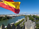 Spanish flag fluttering with city and river in background, Seville, Spain