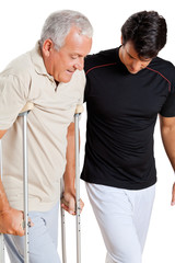 Trainer Helping Senior Man With Crutches