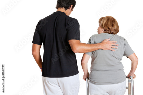 Trainer Assisting Senior Woman With Her Walker