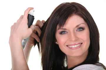 Woman applying hairspray