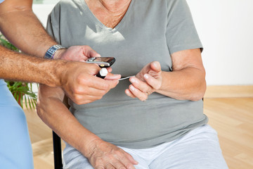 Man Checking Blood Sugar Level Of Patient