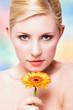 junge lächelnde Frau mit Gerbera-Blüte