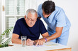 Male Nurse Helping Senior Man In Solving Puzzle