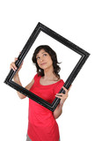 Fototapety Young woman carrying black frame, studio shot