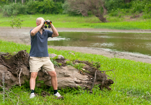 Slim bald man watching the nature through binoculars