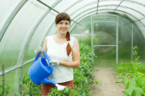 woman watering in greenhouse