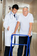 Doctor Assisting Senior Man On a Walker