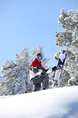 Man snowboarding down snowy hill