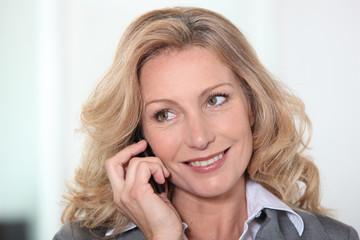Portrait of blond mature woman having phone call