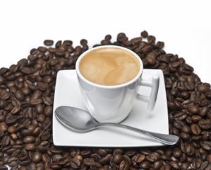 Café espresso sobre un montón de granos de café.