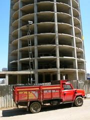 Roter Lastwagen vor dem Gerippe eines Hochhaus Neubaus