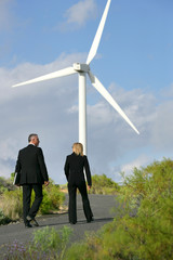 Man and woman in suit walking next to a wind turbine