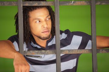 Man posing behind bars
