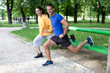 Happy young couple exercising outdoors, using a park bench to do