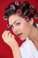 Woman with curlers putting on makeup