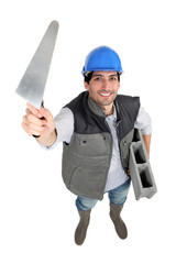 Bricklayer with trowel and cement block